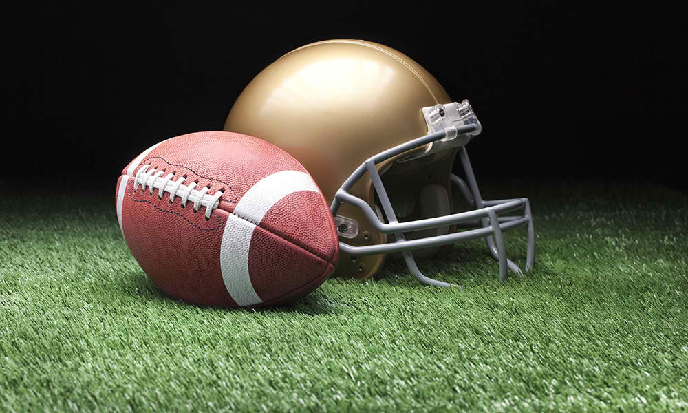 Football_and_Helmet_Dark_Background_FEATURED-IMAGE_iStock-477432593